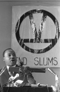 """Martin Luther King Jr. with a sign that says """"End Slums"""""""