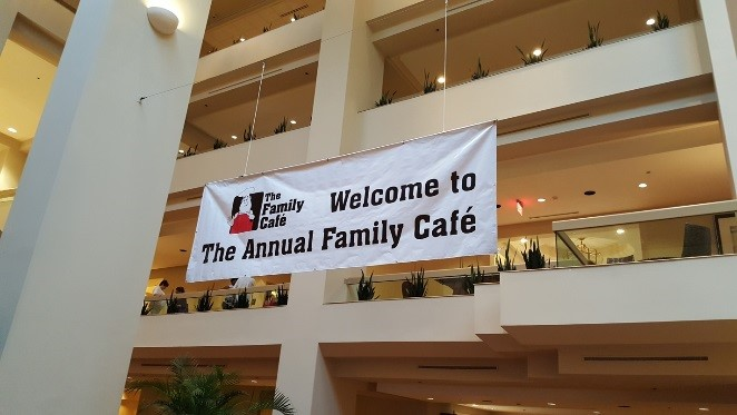 "A banner hangs from inside a multiple-story building that has a man in a chef's hat (the Family Cafe logo) and the words ""Welcome to the Annual Family Cafe"""")"