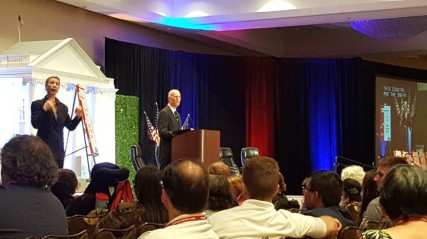 Governor Rick Scott speaks to a crowd from behind a podium. A sign language interpreter signs to his right.